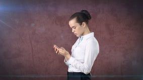 Молодой милый конец коммерсантки вверх по портрету держа мобильный телефон в ее руках и наблюдая его Изолированная предпосылка ст Стоковая Фотография RF
