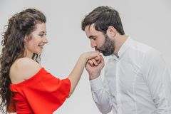 Молодой милый мальчик целует его красивую девушку красиво Во время этой девушки одетой в красном платье, парень в белой рубашке стоковая фотография rf