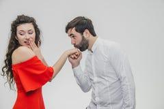 Молодой милый мальчик целует его красивую девушку красиво Во время этой девушки одетой в красном платье, парень в белой рубашке стоковые фото