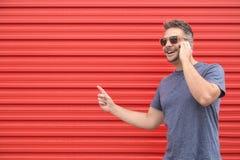 Молодой модный человек звоня телефонный звонок против красной предпосылки стоковое фото rf