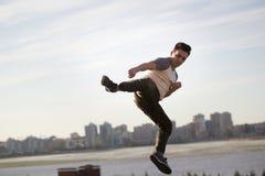 Молодой мужской боец пинком выполняет циркаческий пинок перед горизонтом Стоковое Фото
