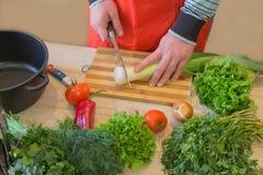 Молодой мужской варить в кухне еда здоровая Подрезанное изображение овощей вырезывания молодого человека для еды Стоковая Фотография
