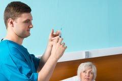 Молодой мужской доктор в форме получает готовым сделать впрыску Стоковые Фотографии RF