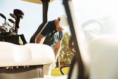 Молодой мужской игрок в гольф стоя на тележке гольфа стоковое фото