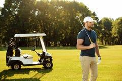 Молодой мужской игрок в гольф с положением гольф-клуба стоковое фото