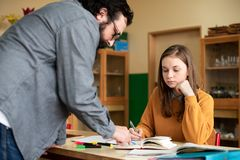 Молодой мужской испанский учитель помогая его студенту в классе химии Образование, обучая стоковое изображение rf