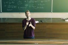 Молодой мужской лектор в рукоплескании лекционного зала с классн классным на заднем плане стоковые фото