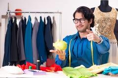 Молодой мужской портной работая на мастерской стоковое изображение rf