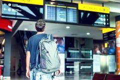 Молодой мужской путешественник с рюкзаком смотрит информацию b стоковая фотография