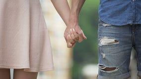 Молодой мужчина и женский принимая один другого вручную и позволяющ идут, говорить до свидания видеоматериал