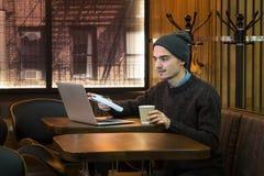 Молодой мужчина обсуждая или говоря над интернетом в кафе Стоковые Фотографии RF