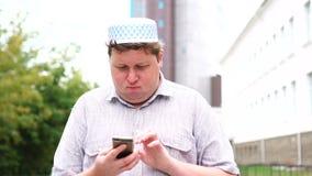 Молодой мусульманский человек в городе идя используя мобильный телефон видеоматериал