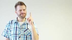 Молодой небритый кавказский человек в рубашке стоящ и развевающ его палец, идея, дизайн, белая предпосылка, конец-вверх, экземпля видеоматериал