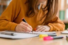 Молодой непознаваемый женский студент колледжа в классе, принимая примечания и используя highlighter Сфокусированный студент в кл стоковые изображения