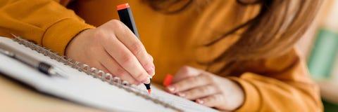 Молодой непознаваемый женский студент колледжа в классе, принимая примечания и используя highlighter Сфокусированный студент в кл стоковое изображение rf