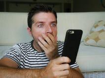 Молодой озадаченный и сотрясенный человек используя мобильный телефон смотря средства массовой информации интернета социальные ил стоковая фотография