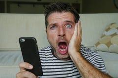 Молодой озадаченный и сотрясенный человек используя мобильный телефон смотря средства массовой информации интернета социальные ил стоковые изображения rf