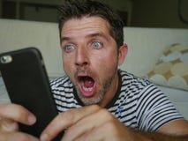 Молодой озадаченный и сотрясенный человек используя мобильный телефон смотря средства массовой информации интернета социальные ил стоковое фото