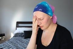 Молодой онкологический больной в головном платке держит голову в руках с стрессом Стоковое Изображение