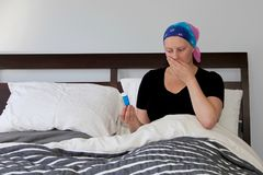 Молодой онкологический больной в головном платке отдыхает в кровати с тошнотой и смотрит пилюльки с отвращением Стоковое фото RF