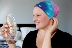 Молодой онкологический больной в головном платке смотрит собственную личность в зеркале и улыбках стоковое изображение