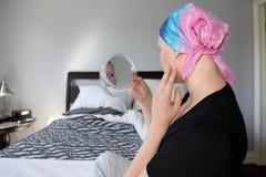 Молодой онкологический больной в головном платке смотрит сотрясенным на ее отражении в зеркале Стоковое Фото