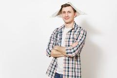 Молодой опытный красивый человек в случайных одеждах и шляпе газеты держа руки сложенный изолированными на белой предпосылке стоковое изображение