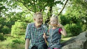 Молодой отец дует пузыри мыла и играет с его дочерью в замедленном движении вполне HD парка лета видеоматериал
