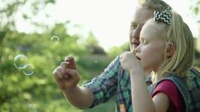 Молодой отец дует пузыри мыла и играет с его дочерью в замедленном движении вполне HD парка лета сток-видео