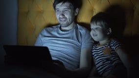Молодой отец и его маленький сын смотря кино шаржа используя портативный компьютер пока лежащ в кровати в выравниваться дома Стоковая Фотография