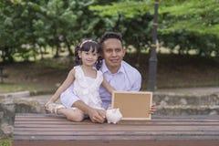Молодой отец научить его дочери к сохраняя деньгам в копилку на лучшее будущее стоковые изображения rf