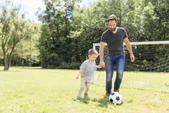 Молодой отец при его маленький сын играя футбол на футбольном поле стоковые фотографии rf