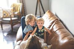 Молодой отец с дочерью и сыном младенца на софе дома стоковые изображения rf