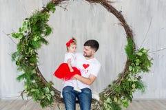 Молодой отец с дочерью младенца имея потеху пока сидящ в отбрасывать внутри помещения стоковые фото