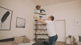 Молодой отец с его маленький играть сына Сын отца бросая в воздухе, slomo акции видеоматериалы