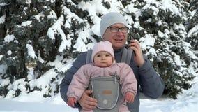 Молодой отец с его младенцем в несущей с отцом телефона говоря работая сток-видео