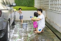 Молодой отец уча, что его дети помыли автомобиль стоковые фотографии rf
