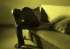 Молодой отчаянный унылый и разочарованный человек горюя дома проблема депрессии кресла софы страдая и плакать кризиса тревожности стоковое изображение rf
