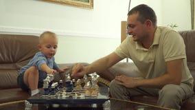 Молодой папа играя шахматы с его маленьким сыном акции видеоматериалы