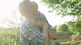Молодой папа тратя время с его сыном в парке лета держа его и играя замедленное движение вполне HD сток-видео