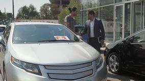 Молодой парень выбирает автомобиль в автосалоне outdoors и разговаривать с продавцом видеоматериал