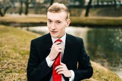 Молодой парень в черном костюме выправляет его красную связь человек белокурый с ручкой в его руках стоковая фотография