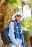 Молодой парень в шляпе, солнечных очках, шарфе, с рюкзаком стоит Стоковое Изображение RF