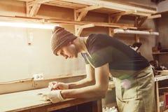 Молодой парень делая метки на древесине в joinery стоковые изображения
