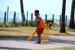 Молодой парень играя сверчка на улице стоковое фото rf