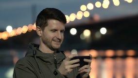 Молодой парень печатает сообщение на мобильном телефоне и усмехаться Конец вверх выглядит хорошим видеоматериал