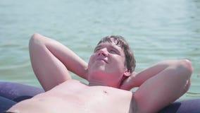 Молодой парень плавает в море на раздувном тюфяке взволнованности положительные лето дня горячее сток-видео