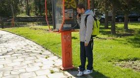 Молодой парень принимая приемник таксофона, положение и удерживание знонят по телефону на ухе видеоматериал