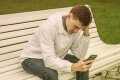 Молодой парень сидит на стенде и читает неприятное сообщение стоковые фото