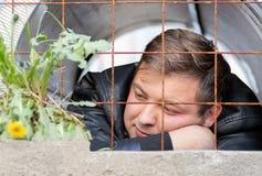 Молодой парень сидя в тюрьме смотря растущ за ржавым цветком одуванчика решетки Мечты пленника свободы стоковое изображение rf